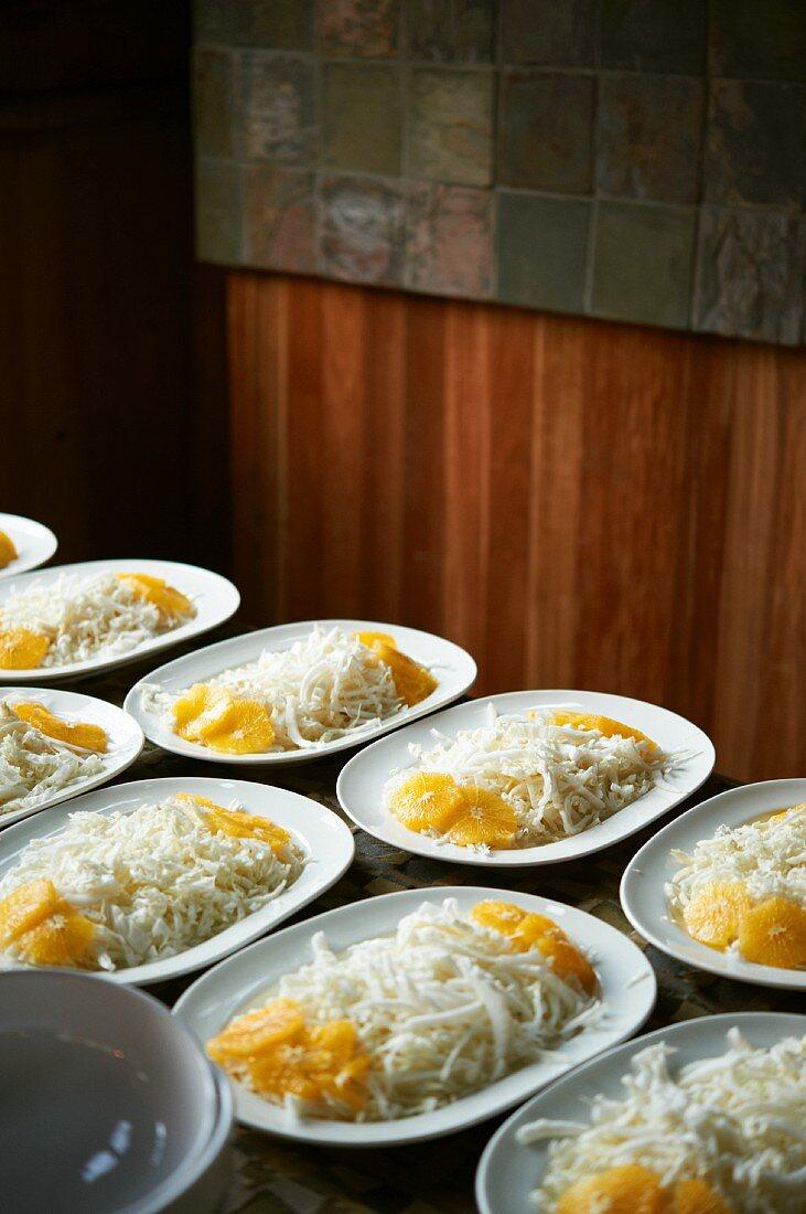 Many Plates of Asian Slaw with Orange Slices