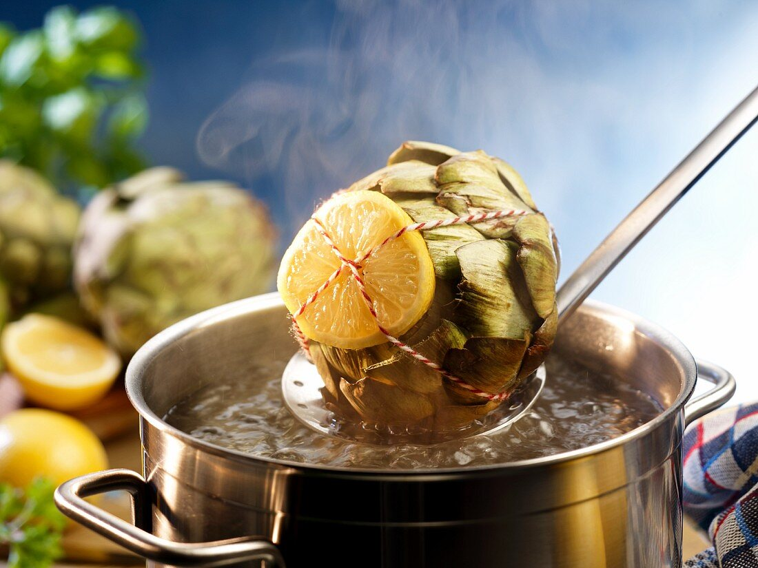 Artichokes with lemon slices being added to boiling water