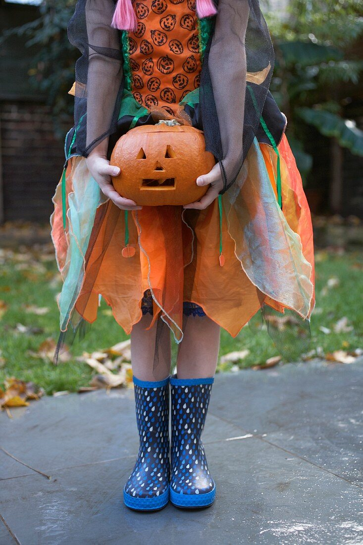A woman dressed as a pumpkin holding a Jack-O lantern