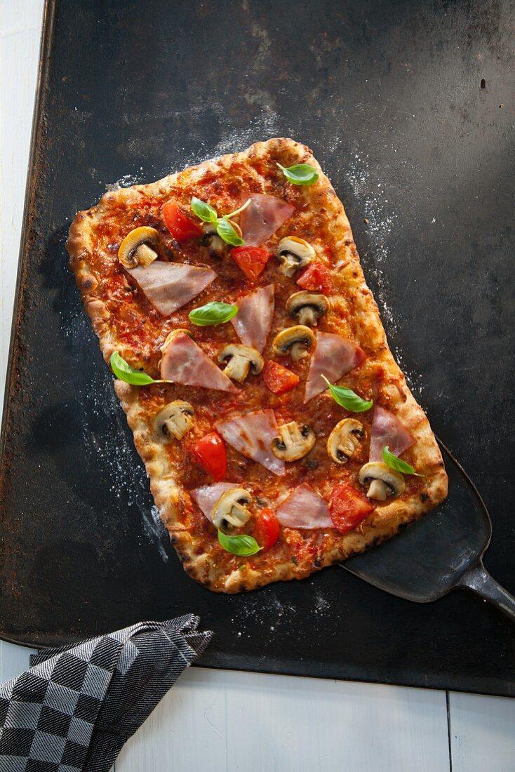 Ham, mushroom and tomato tray bake pizza (seen from above)