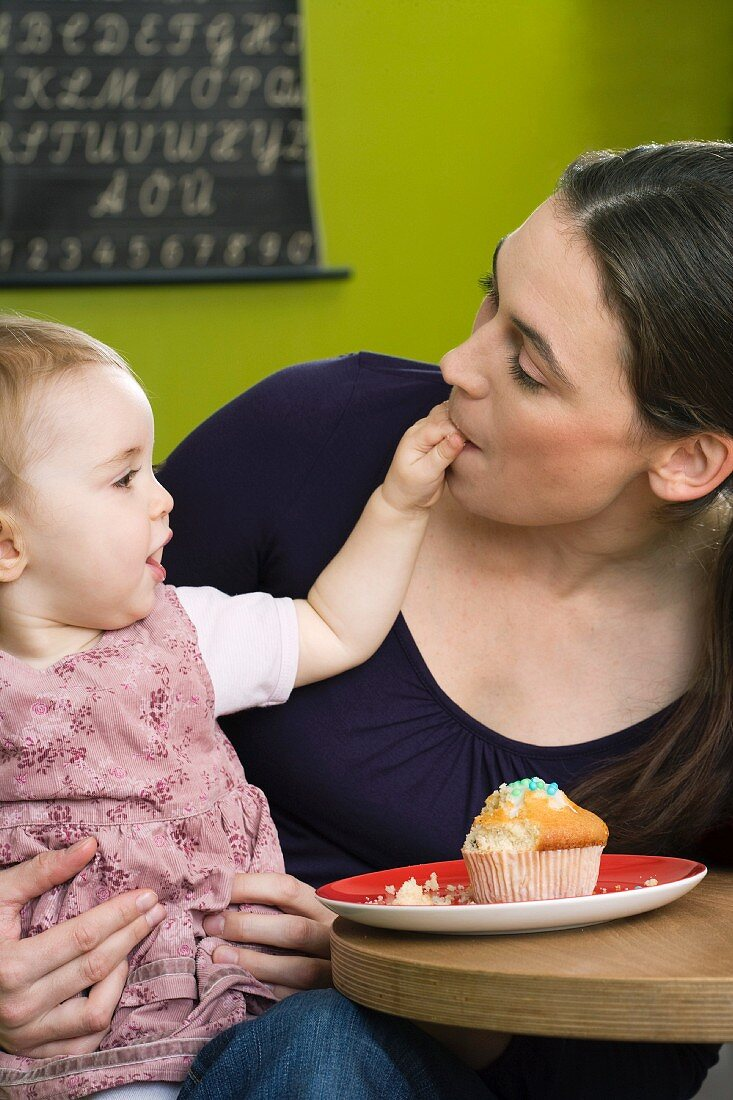 Young girl feeding her mother with cake