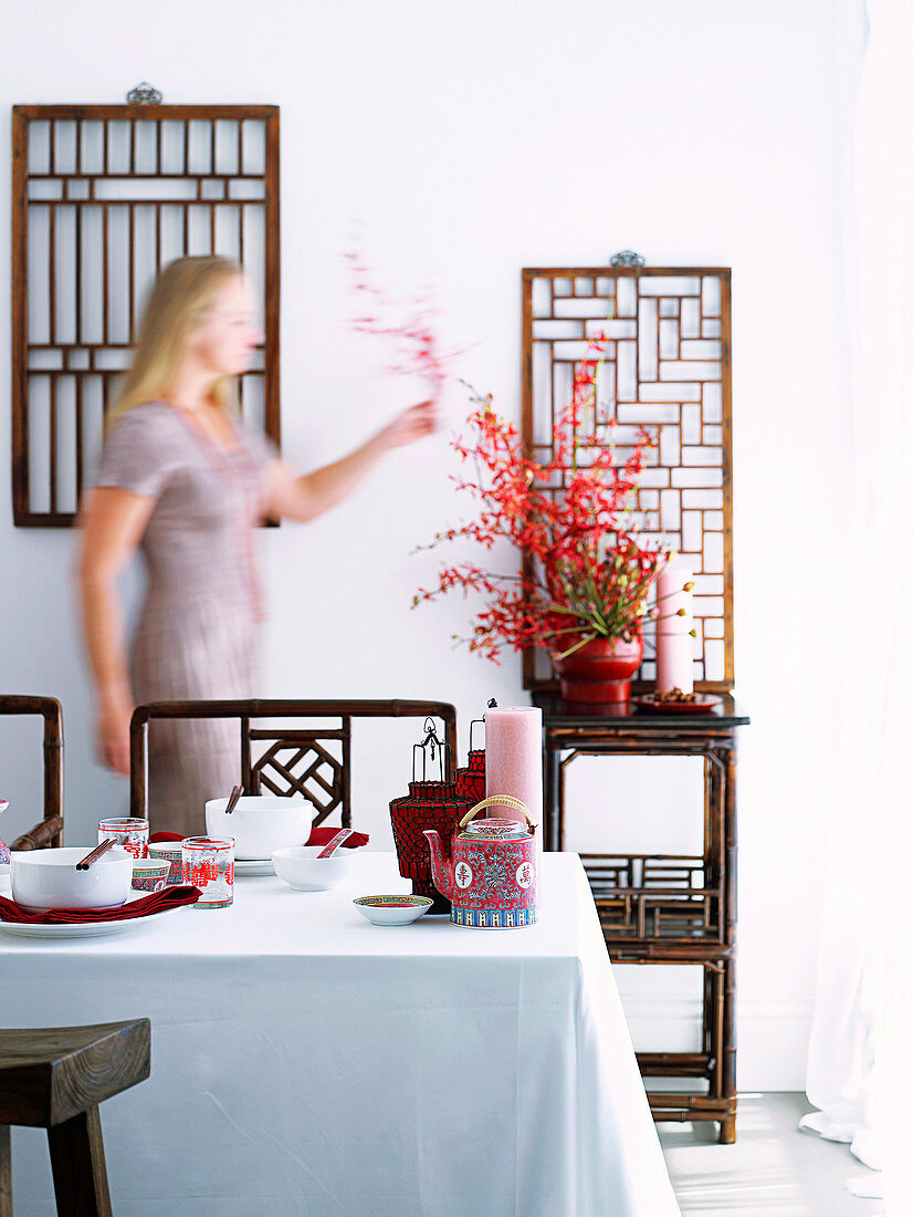 A dining table laid in the Chinese style; in the background, chairs and an occasional table made from bamboo wood