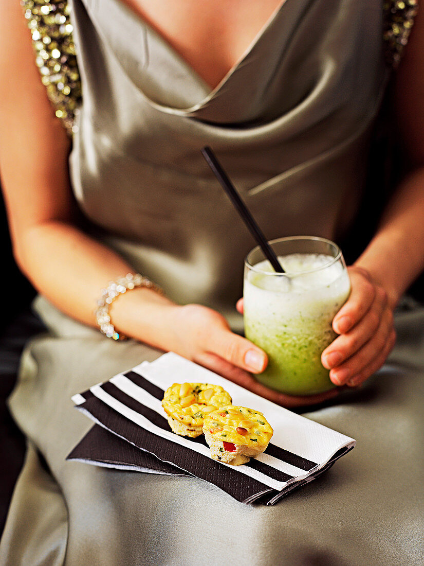 A woman with a cocktail and savoury muffins