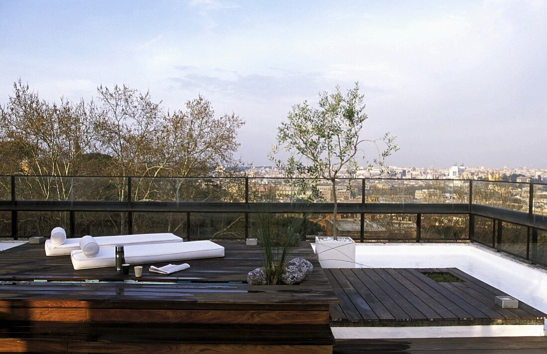 Loungers on a wooden podium on a roof terrace with a view over the city