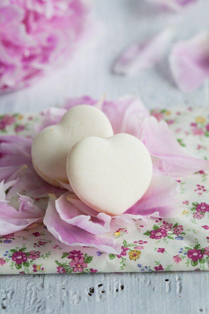 Heart-shaped vanilla macaroons on peony petals