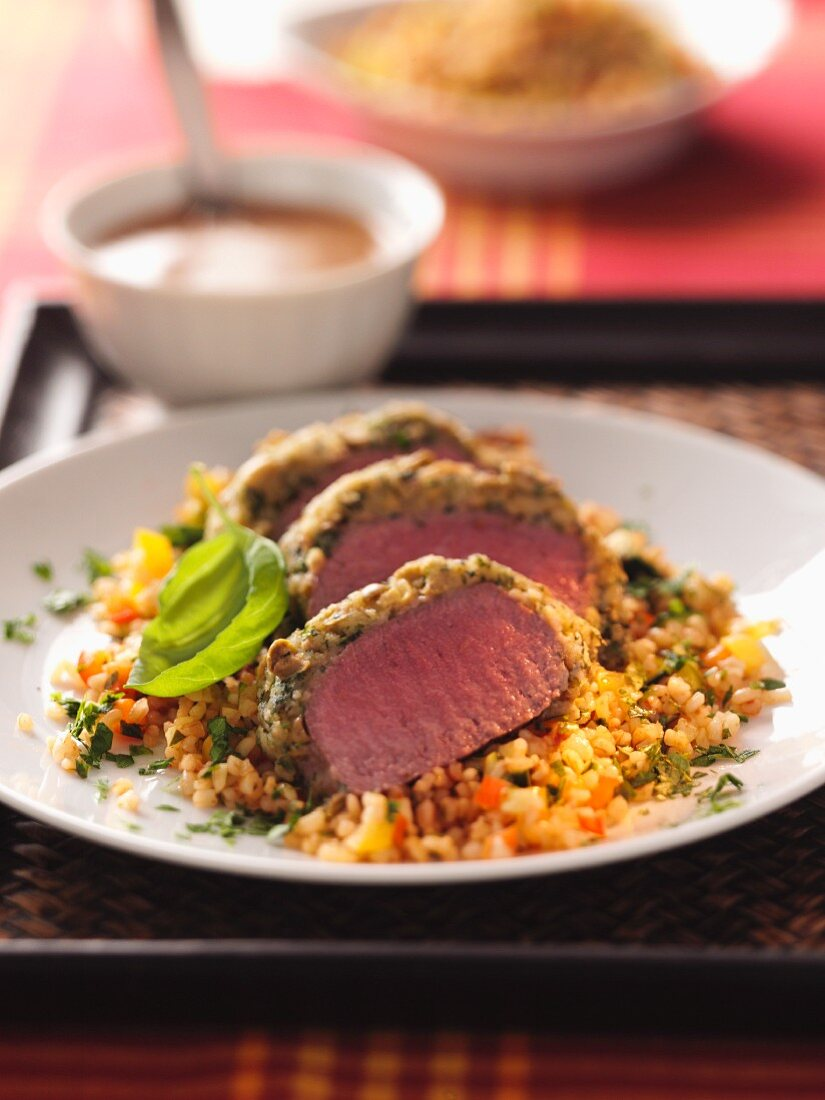 Saddle of lamb with a crust on a bed of barley salad