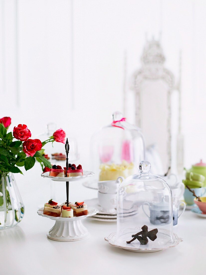 A table with a feminine touch - an elf under a glass cover, delicate cake stand and bouquet of roses. In the background a throne like white chari