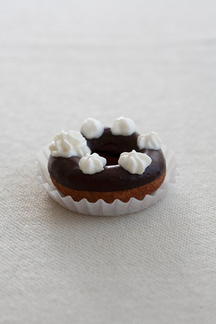 A doughnut with chocolate glaze and blobs of cream