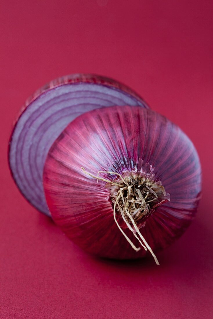 A halved red onion on a red surface