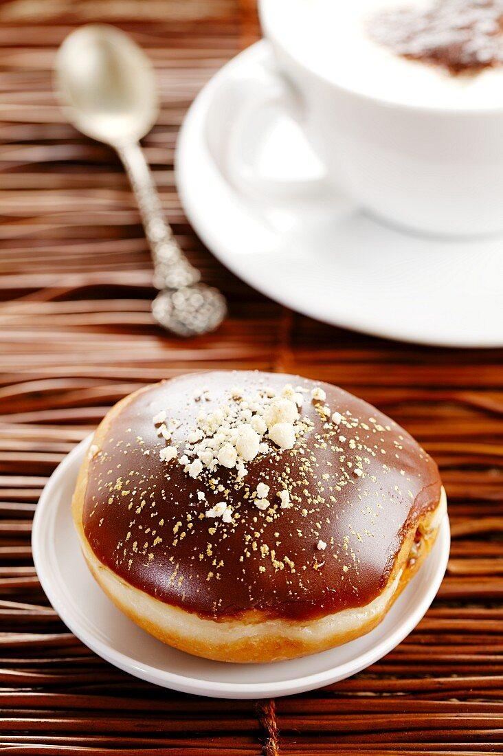 A chocolate doughnut and a cappuccino