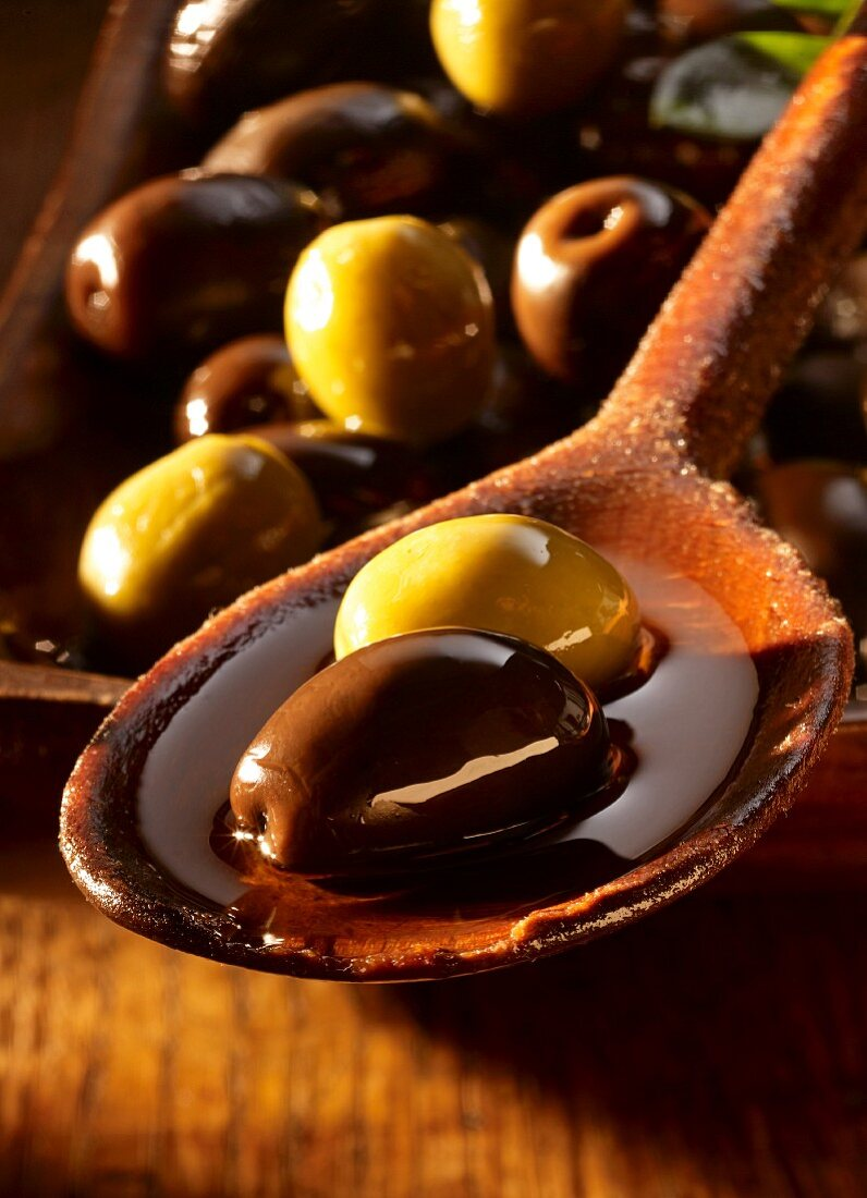 Black and green olives in olive oil on a wooden spoon and in a dish