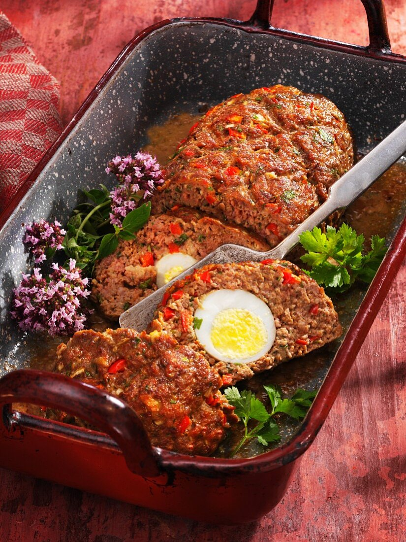 Minced meat filled with egg in a roasting tin