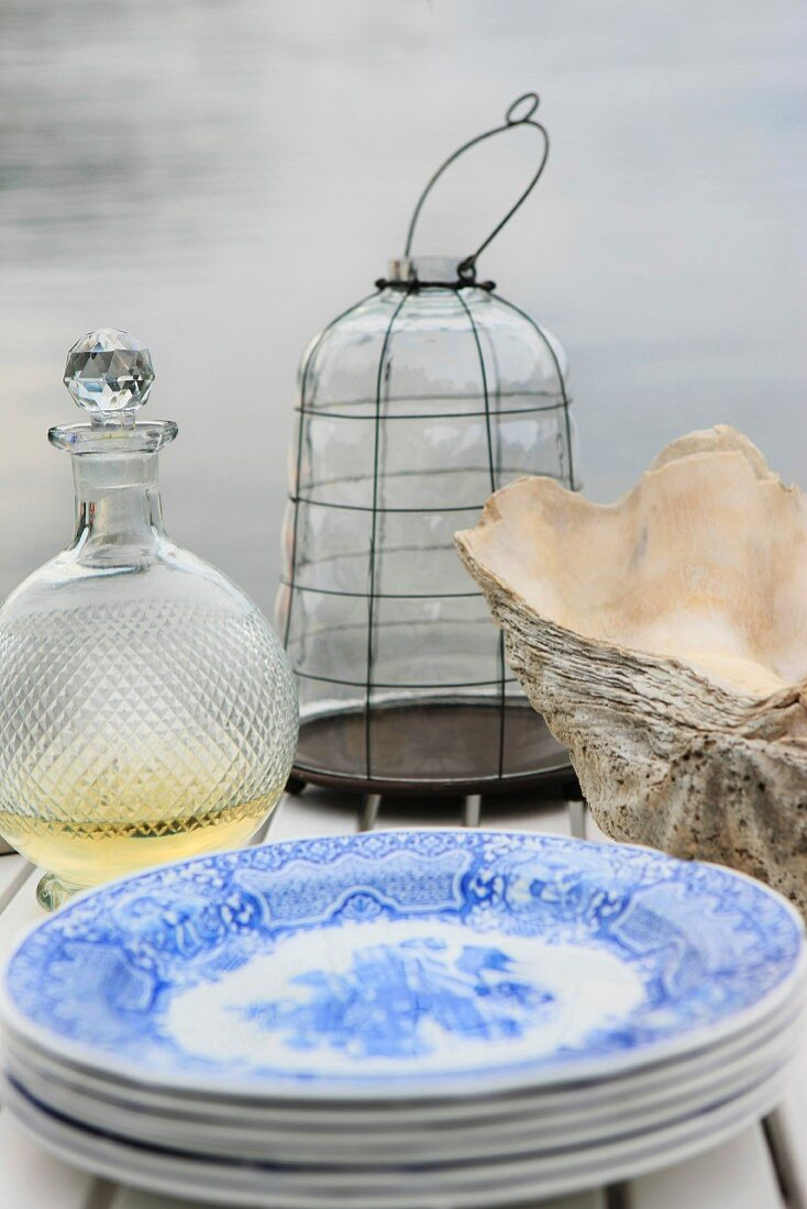 A stack of plates, a carafe, clamshells and a hurricane lamp on a wooden table