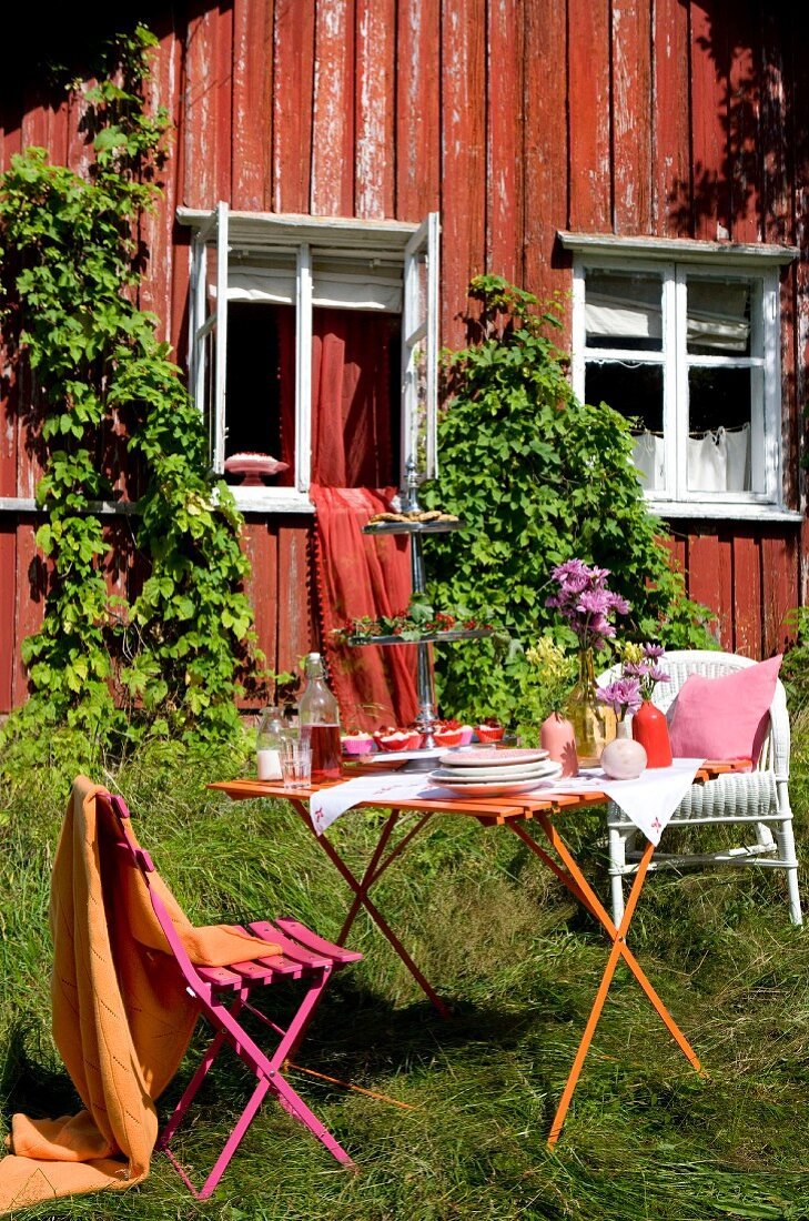 Set garden table in front of wooden cabin