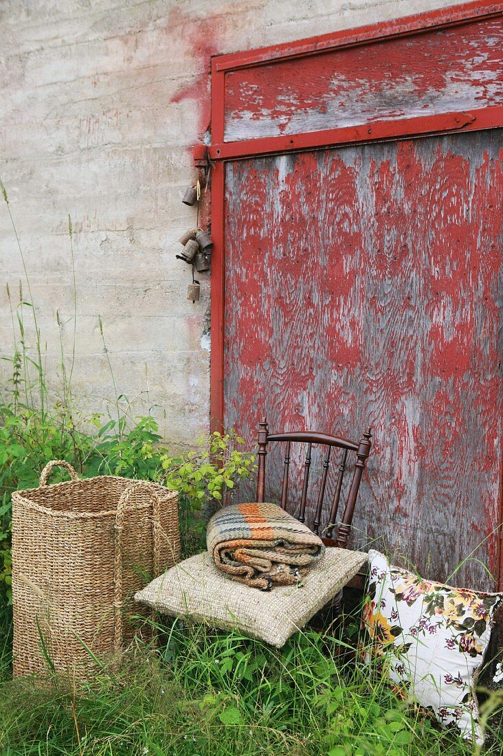 Basket, cushion, blanket and chair in front of barn door
