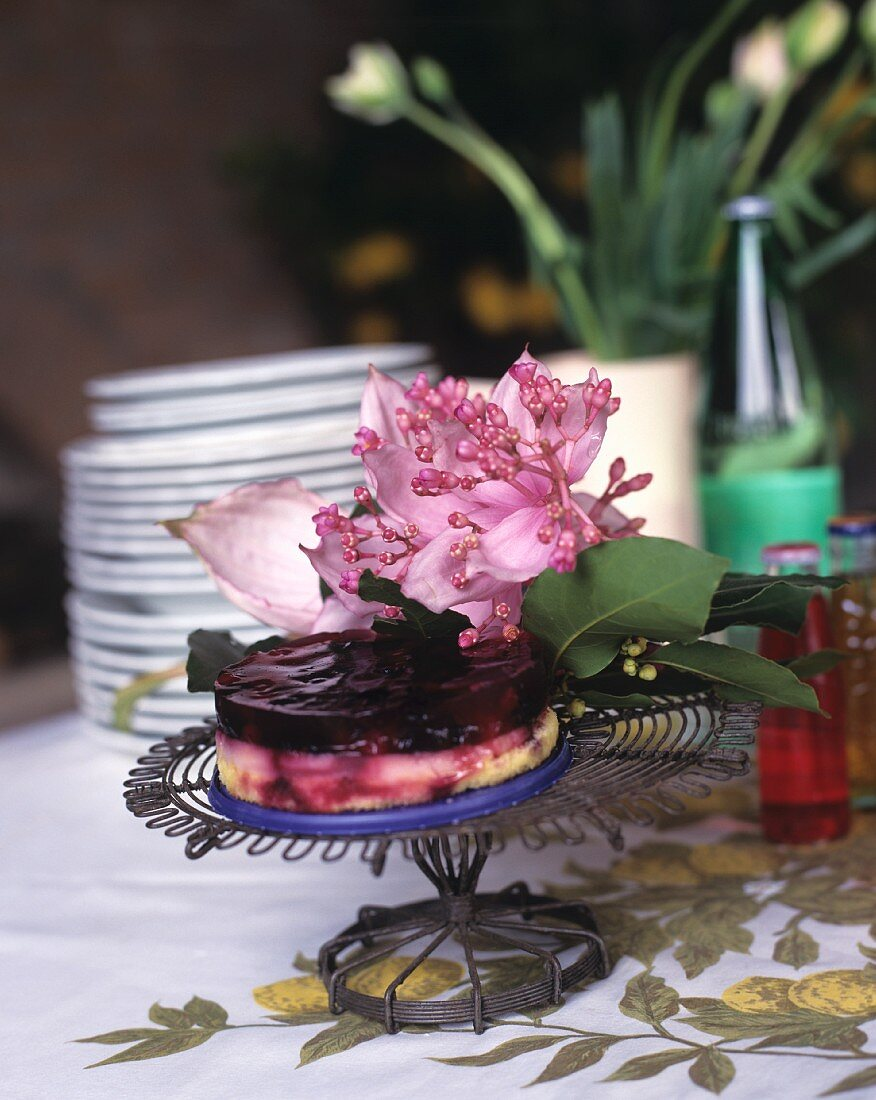 Cake stand with elegant floral decoration and blueberry cake