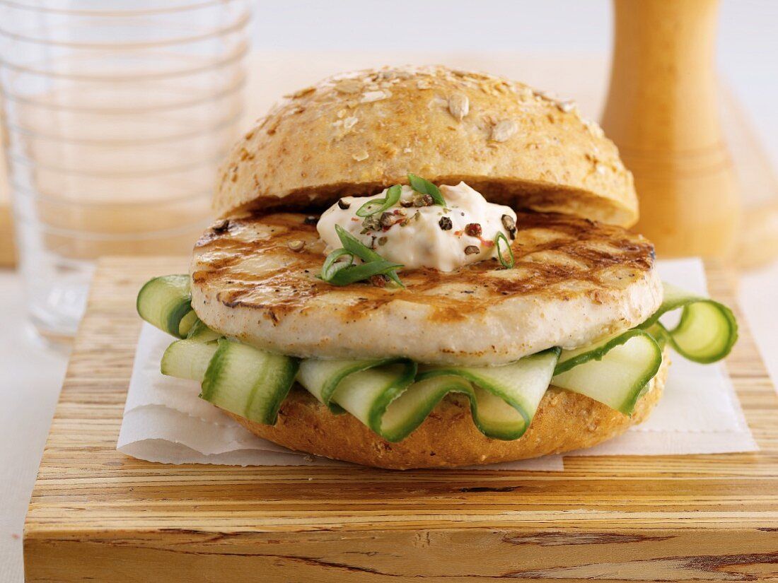 A chicken burger with aioli and cucumber