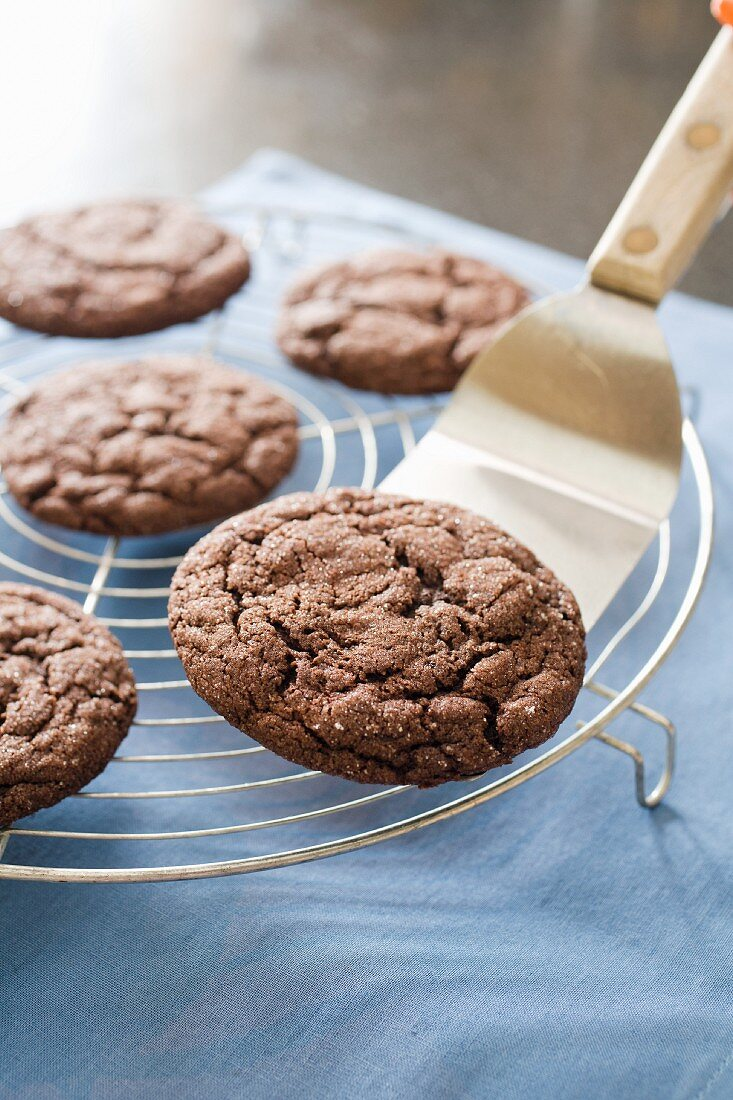 Placing Chocolate Cookies on a Cooling Rack with a Spatula