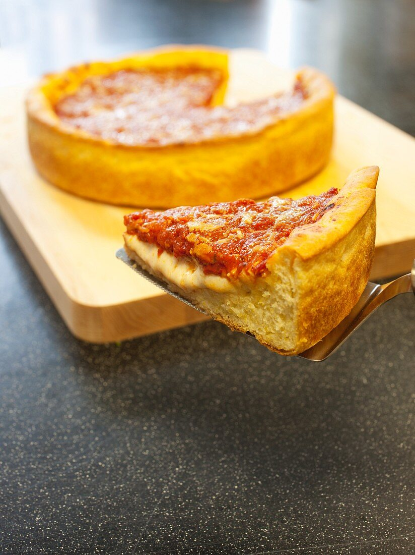 Slice of Deep Dish Pizza on a Spatula; Pizza in Background