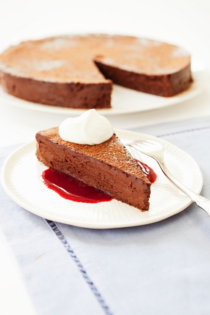 Slice of Flourless Chocolate Cake with Berry Sauce and Whipped Cream; Cake in Background