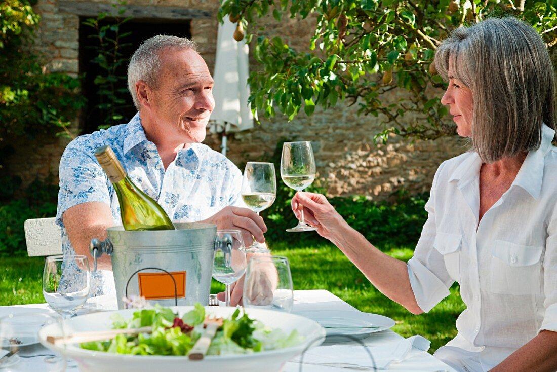 Älteres Paar beim Anstossen mit Weisswein