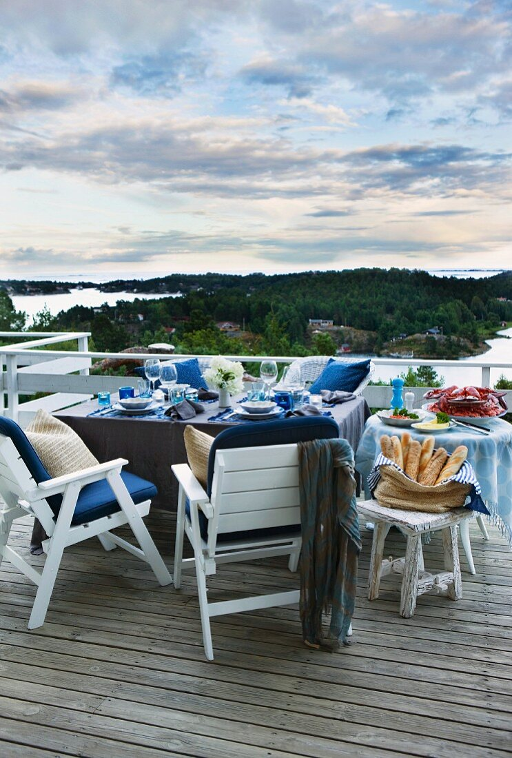 A table laid for a meal on a balcony with a view over the landscape