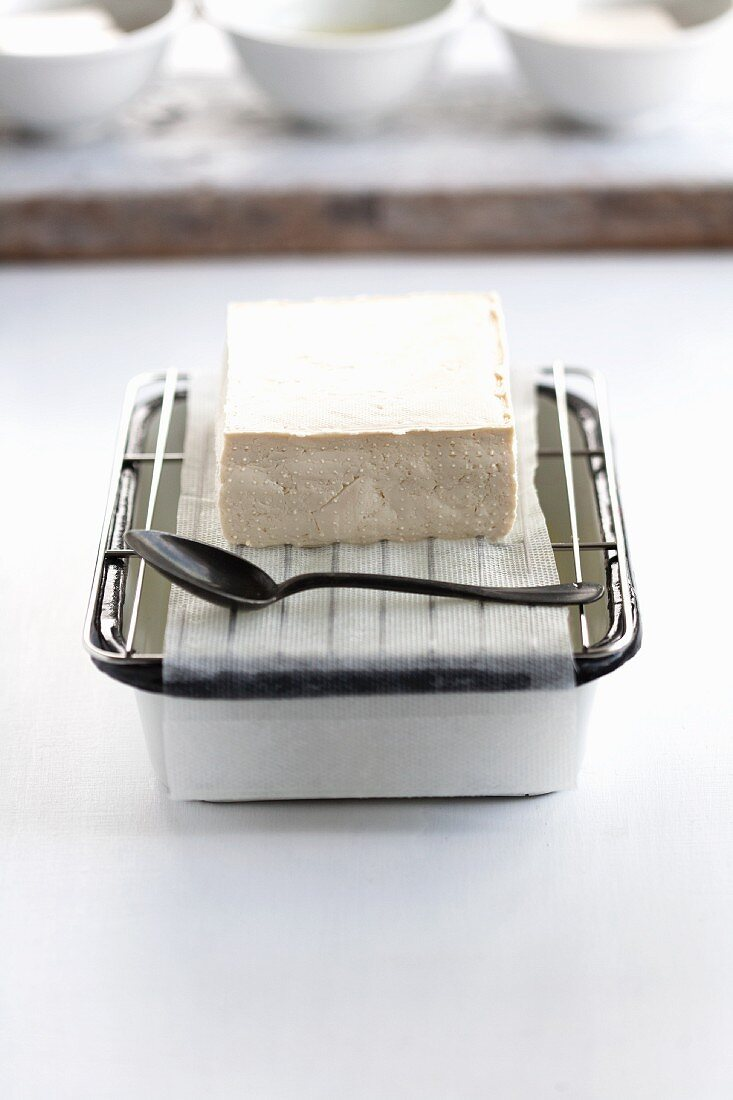 Cotton tofu draining on a grid with fleece