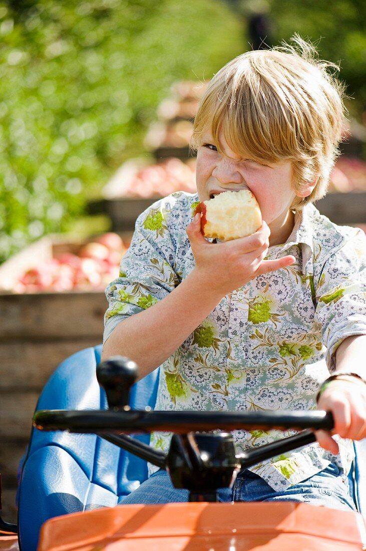 A blond boy eating an apple