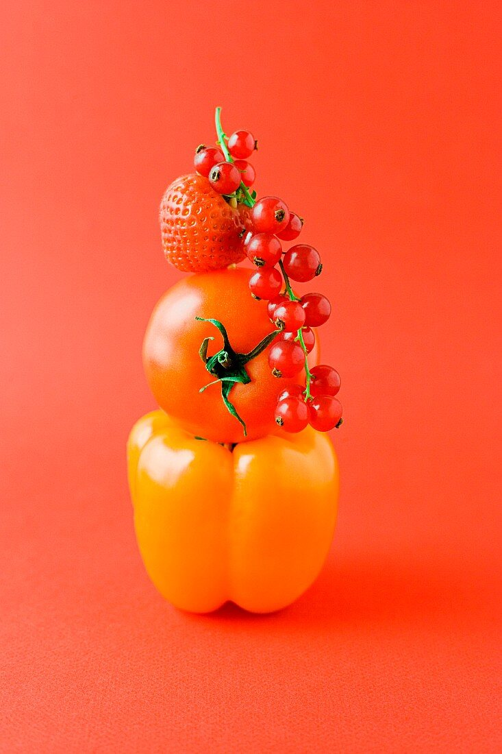 Arrangement of pepper, tomato, strawberry and red currants against orange background
