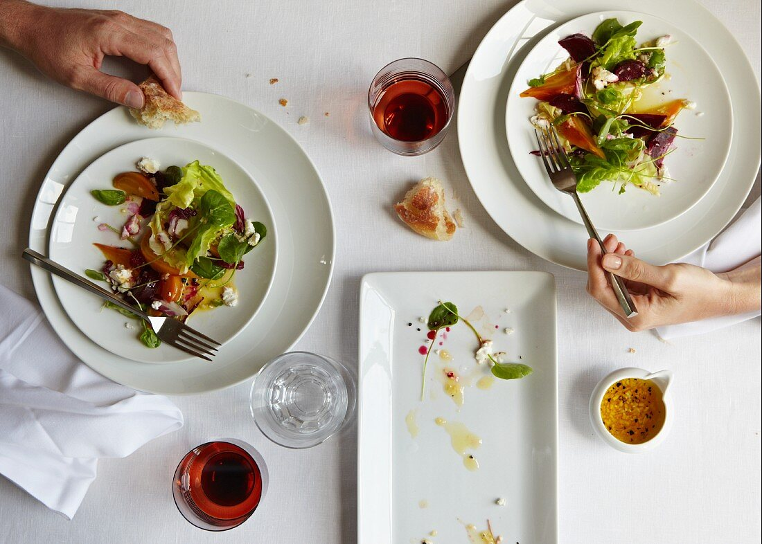 Two Servings of Winter Beet Salad on a Table with Bread; Hands