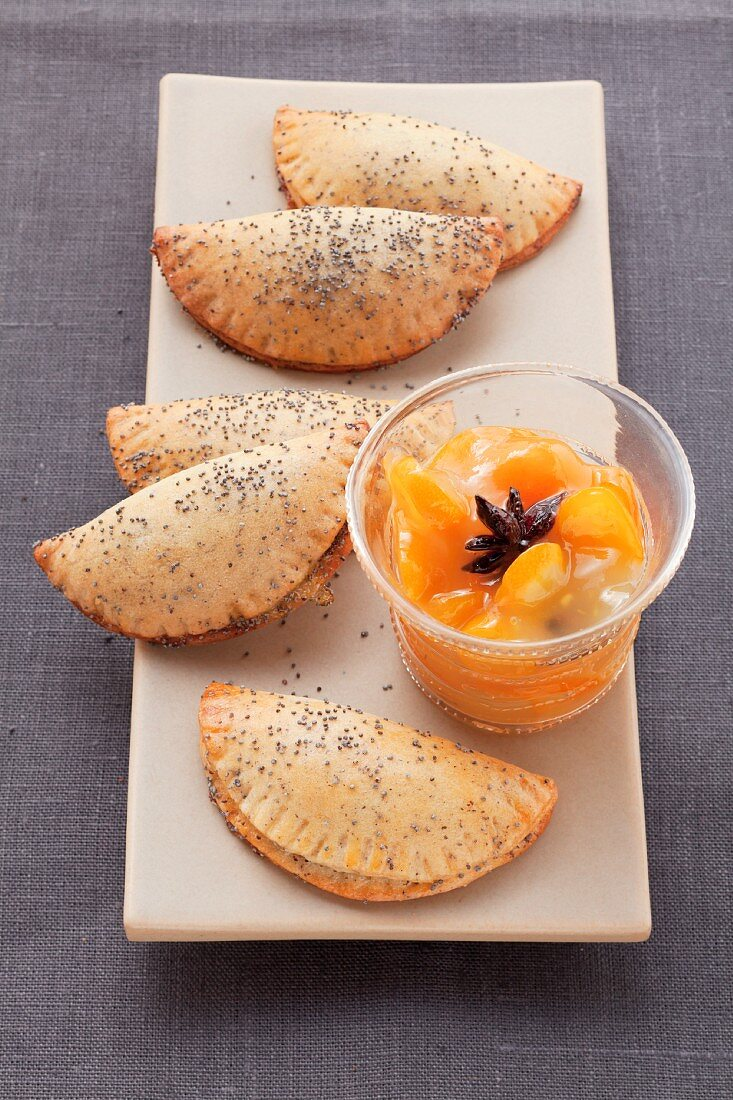 Sweet poppyseed pierogi (steamed dough parcels) with orange dip on an oblong plate