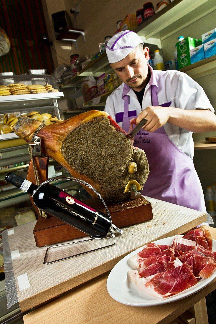 A man cutting pepper ham