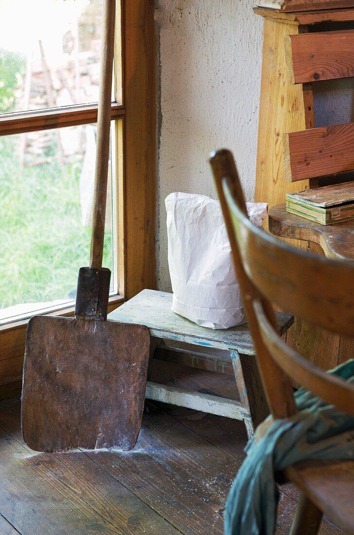 Wooden peel & wooden stool in corner of kitchen