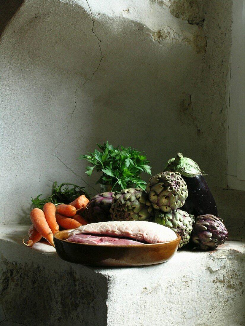 Duck breast, aubergine, artichokes and carrots on plastered sandstone ledge