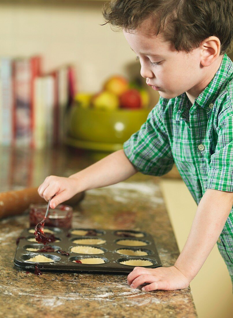 A little boy spooning jam into tarts in a muffin tin