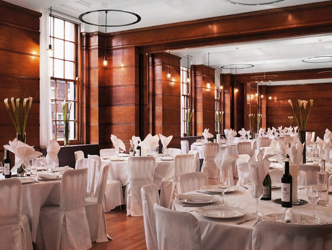 Tables set in white in restaurant with wood-panelled walls