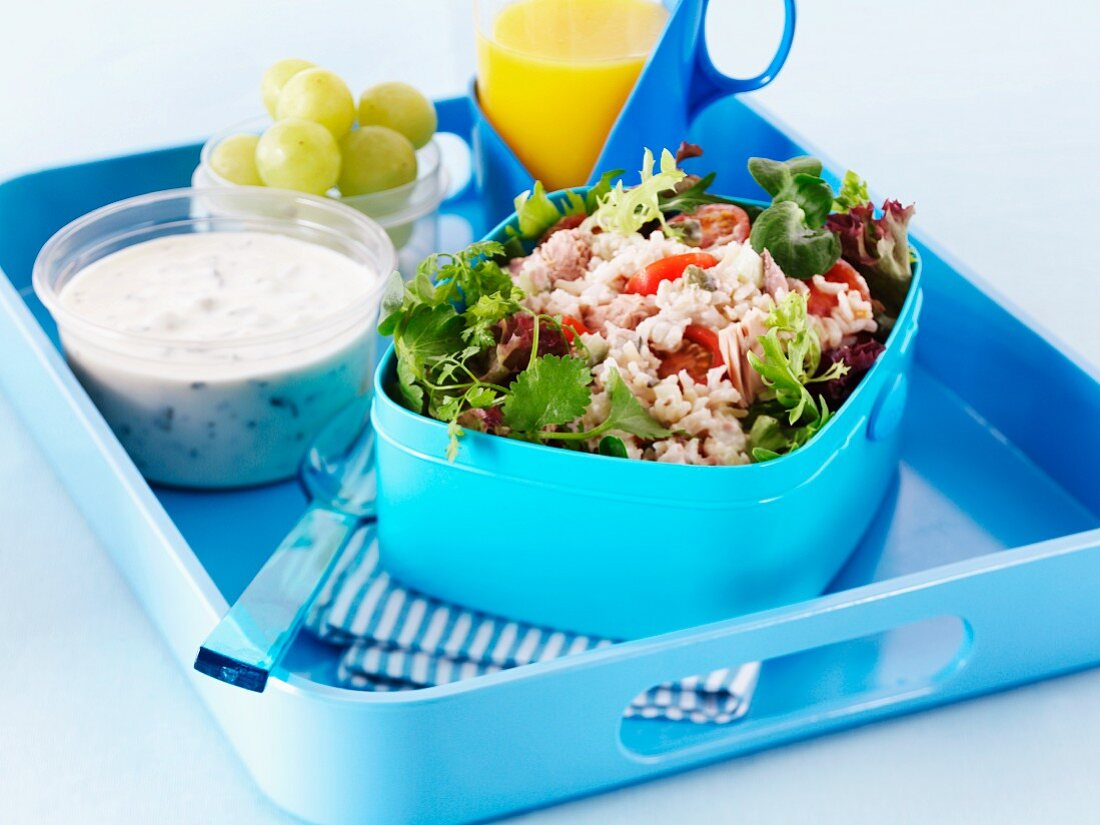 Rice salad, sauce, grapes and orange juice in a lunchbox