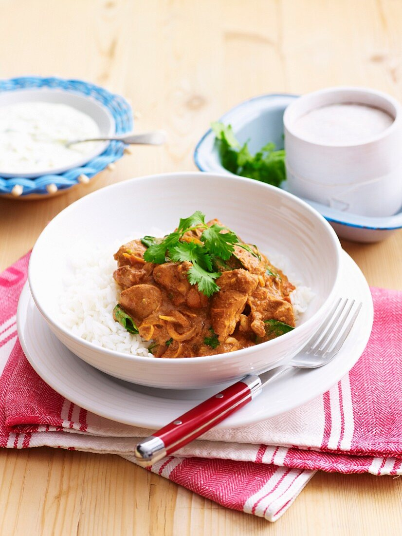 Butter chicken (Indian chicken curry) on a bed of rice with raita