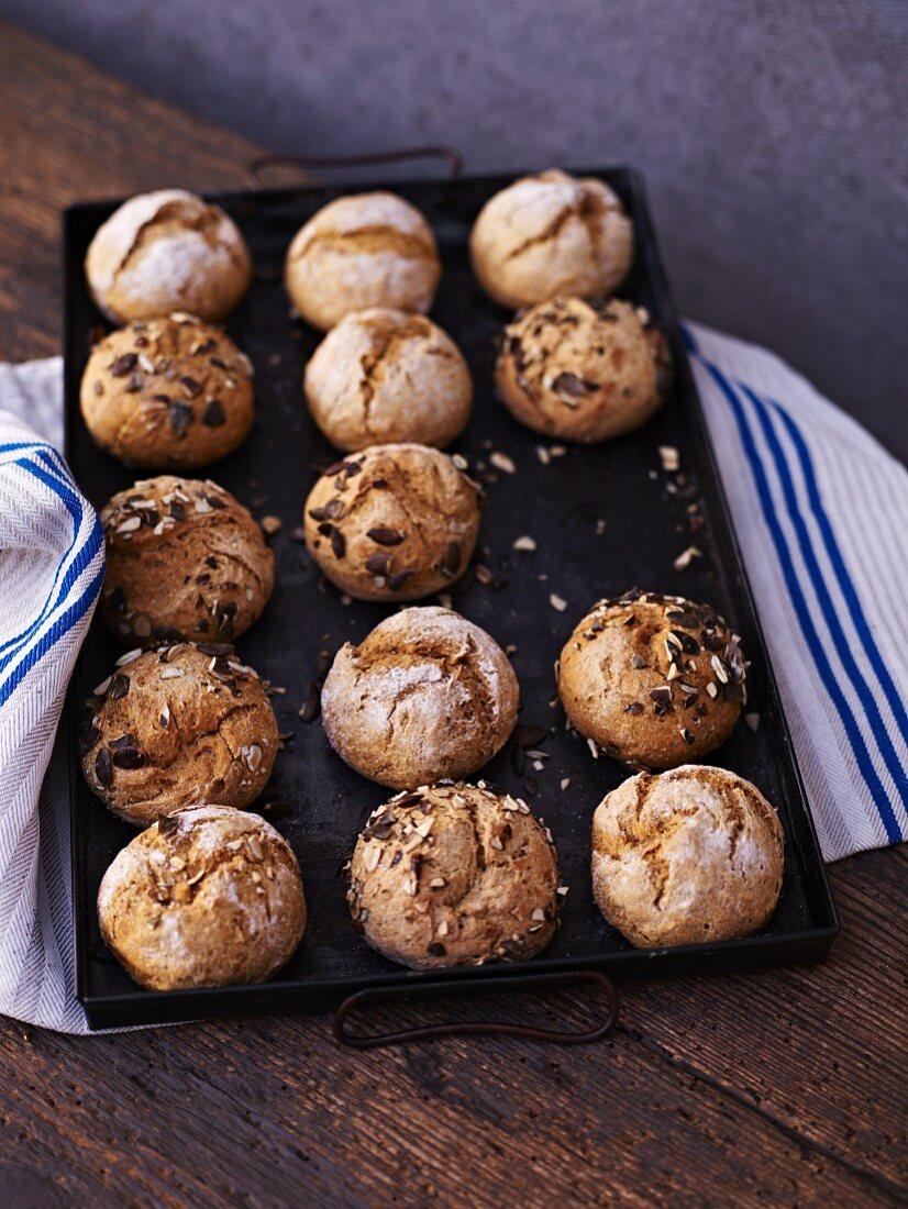 Pumpkin bread rolls on a baking tray; one missing