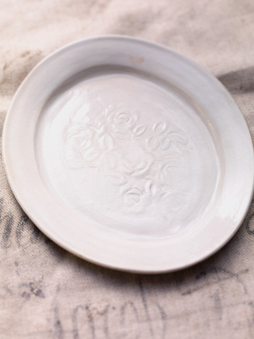 An antique ceramic plate with a rose motif