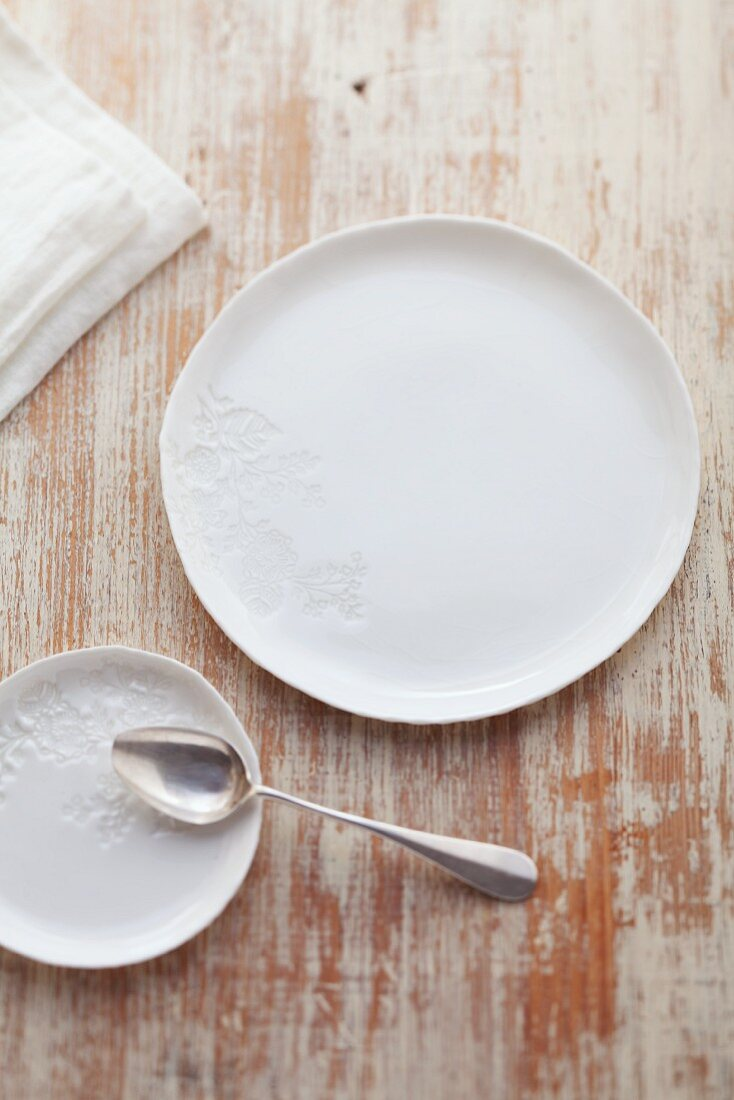 A white porcelain plate and an underplate with a silver spoon