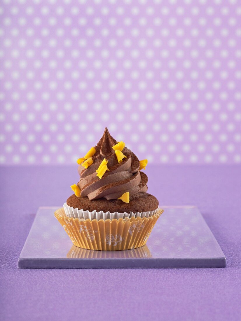 A chocolate cupcake against a purple background