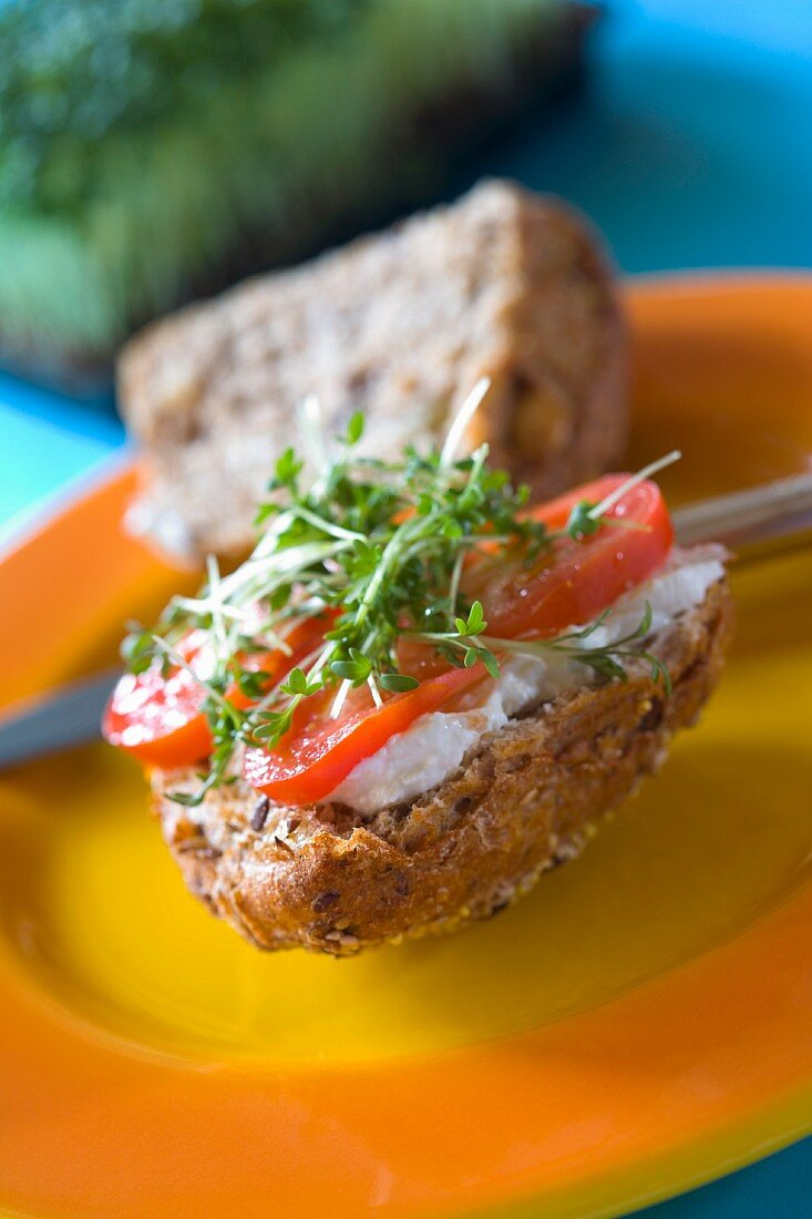 A seeded wholemeal roll with cottage cheese, tomatoes and cress