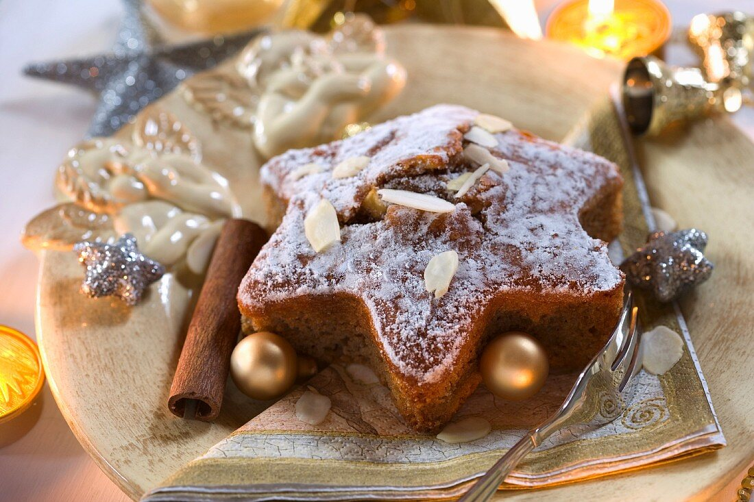 A star-shaped spiced cake with almonds and Christmas baubles on a Christmas angel plate