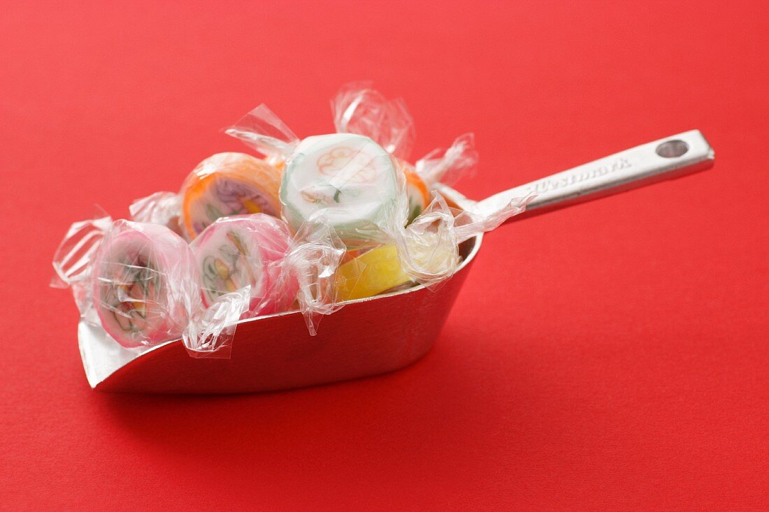 Sugar bonbons in cellophane paper on a scoop