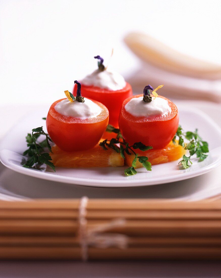 Tomatoes filled with a yoghurt cream on persimmon slices
