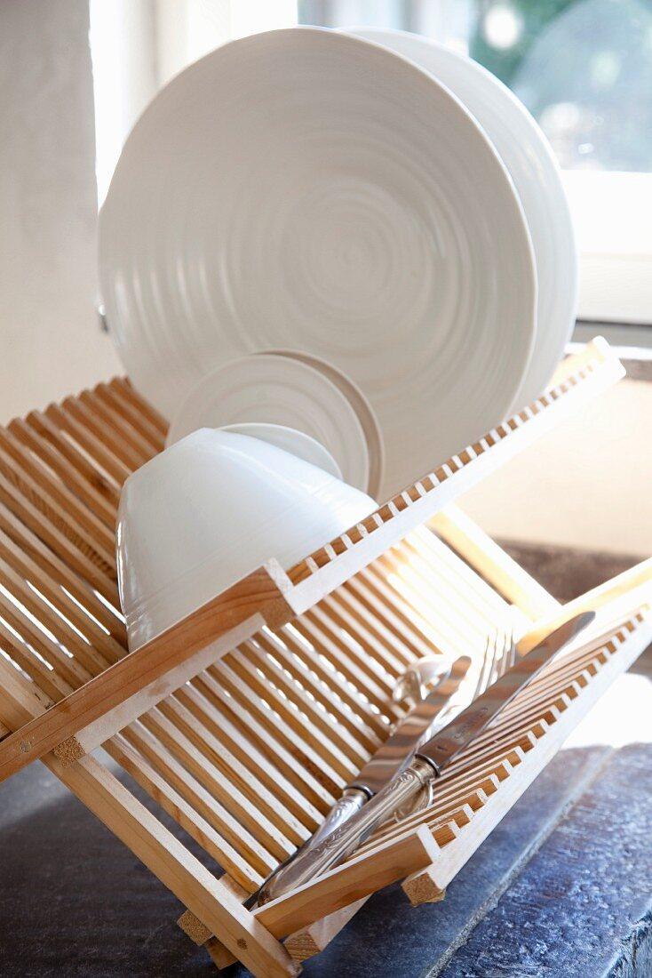 Weisses geschirr und Silbermesser auf Abtropfgestell aus hellem Holz