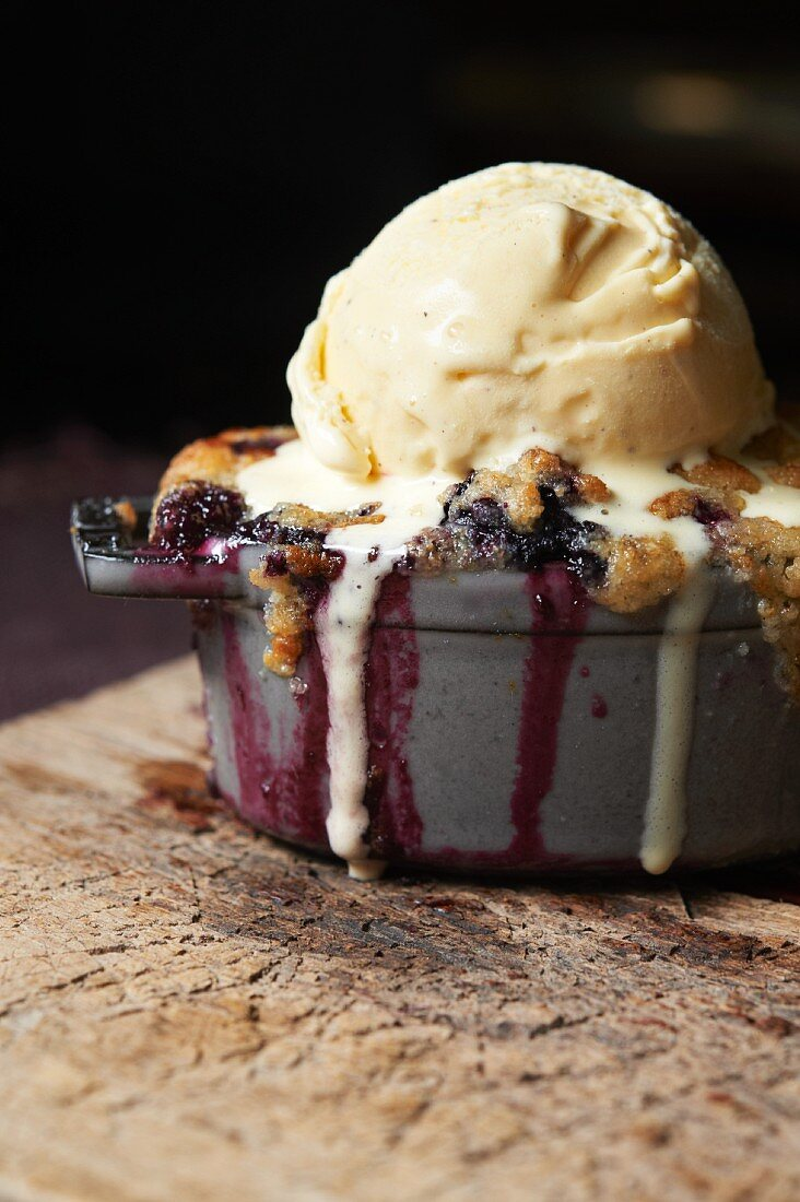 Individual Blackberry Crisp Topped with a Scoop of Vanilla Ice Cream; Melting
