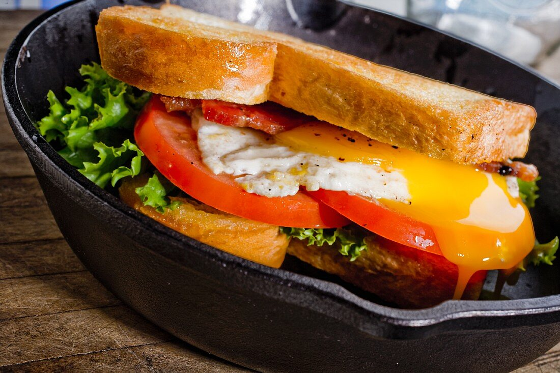 Egg Sandwich with Bacon, Cheese, Tomato and Lettuce on Toasted Bread in aCast Iron Skillet