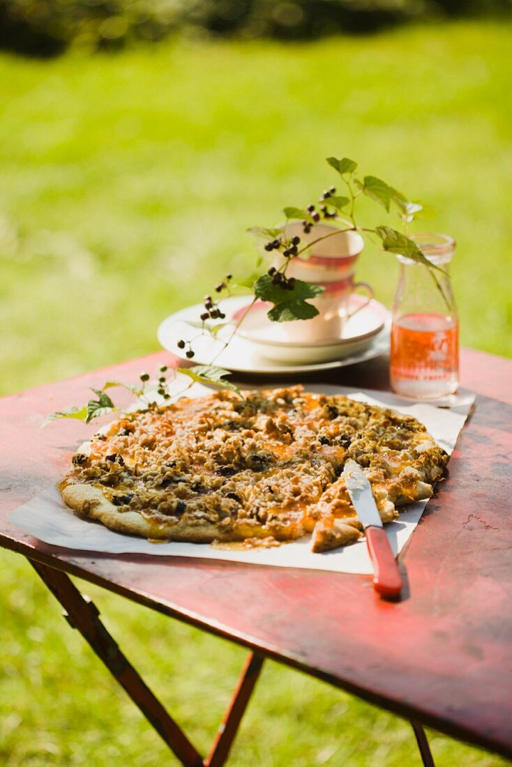 Peach Jam Pizza with Goat Cheese, Nuts and Blueberries; On an Outdoor Table; Blueberry Branch in a Bottle